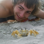 Elliott posing on the beach with a ghost crab